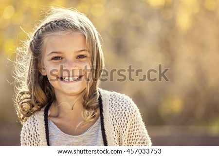 Beautiful Portrait of smiling little girl outdoors. Taking a cute picture on a warm fall day