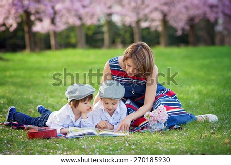 Beautiful portrait of two adorable caucasian boys and their mom, reading a book in a cherry tree blooming garden, spring afternoon, kids lying on the grass on a blanket, vase with flowers and guitar - stock photo