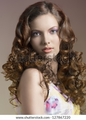 beautiful portrait of young pretty brunette with long curly hair and spring dress  - stock photo