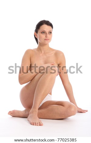 Beautiful pose sitting on floor for a semi nude, beautiful healthy young woman wearing white sports knickers, against white background showing off a sexy fit body. - stock photo