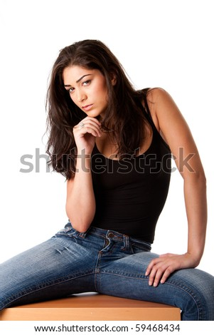 Beautiful posing fashion woman with brown long hair sitting, wearing blue denim jeans and black tank top, isolated. - stock photo