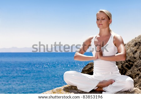 Beautiful positiveblond girl clothing in white sit at the seaside on the rock and meditating in yoga pose