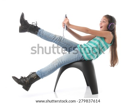 Beautiful pre-teen girl going crazy with a tablet computer and headphones. Isolated - stock photo