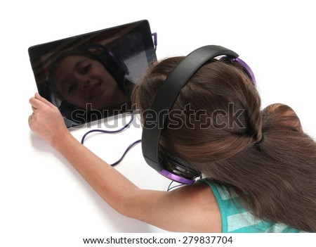 Beautiful pre-teen girl on the floor, using a tablet computer and headphones, white background - stock photo