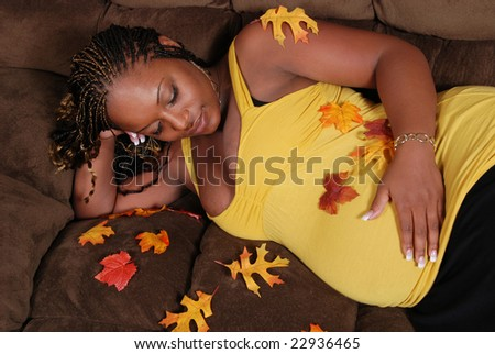 Beautiful pregnant African American woman, laying on the sofa wearing a yellow top. She has autumn leaves scattered on her because her twins are going to be born in autumn. - stock photo