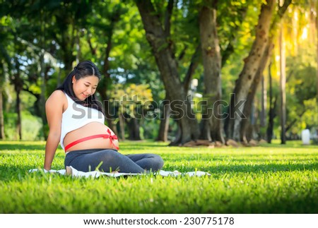 Beautiful pregnant asian woman relaxing in the park with red ribbon - stock photo