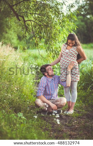 Beautiful pregnant couple hugging outdoors