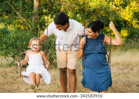 Beautiful pregnant family on old swings in nature in summer - stock photo