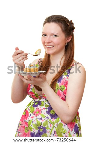 Beautiful pregnant girl is eating cake.