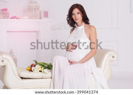 Beautiful pregnant girl with tulip flowers - stock photo
