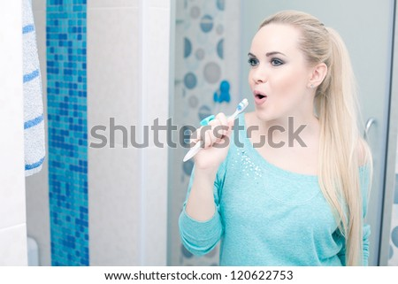 Beautiful pregnant lady having fun: blonde holding her toothbrush and singing a song. Indoor shot.