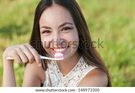 Beautiful pregnant lady holding toothbrush - stock photo