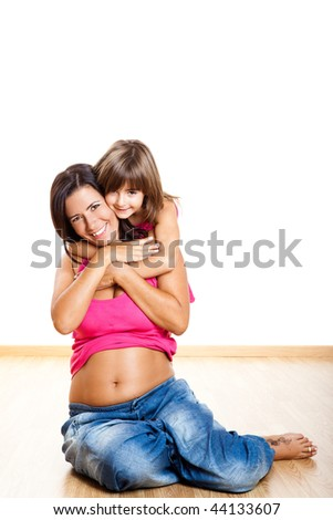 Beautiful pregnant mother with her daughter isolated on white - stock photo