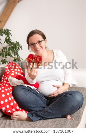 Beautiful pregnant mother with shoes her daughter