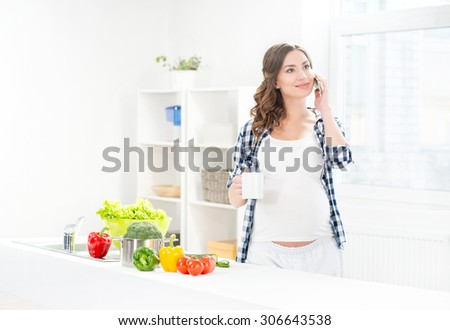 Beautiful pregnant smiling woman surfing smartphone and having a breakfast. - stock photo