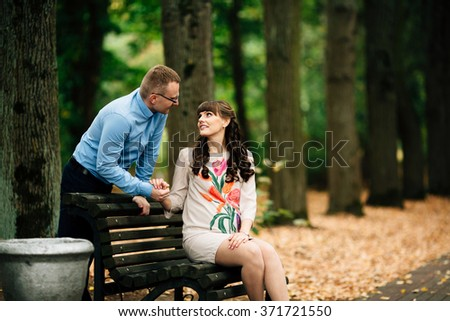 Beautiful pregnant stylish couple relaxing outside in the autumn park sitting on bench. Handsome husband holds his wife's hand. - stock photo