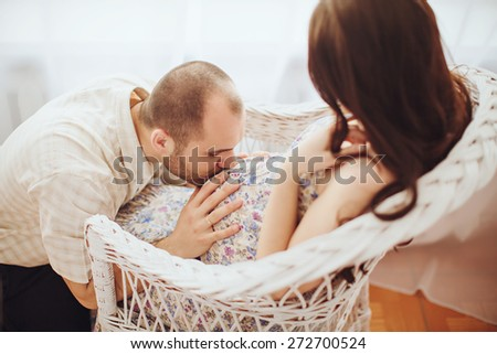 Beautiful pregnant woman and her husband is in their bedroom - stock photo