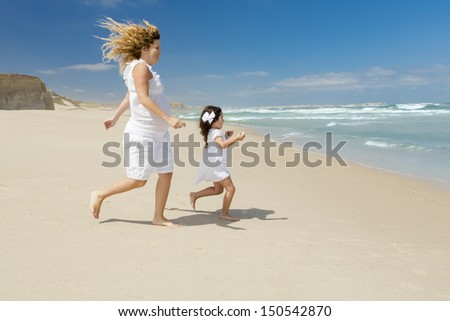 Beautiful pregnant woman and her little daughter running to the sea