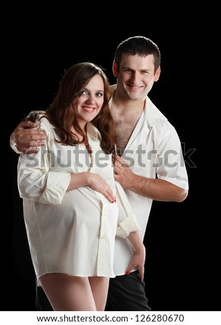 beautiful pregnant woman and man in the studio - stock photo