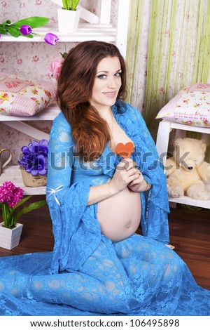 Beautiful pregnant woman at home showing her tummy with teddy bear toys and flowers. Young happy girl in provence interior in bedroom with colored pillows waiting for little baby. sweet pregnancy