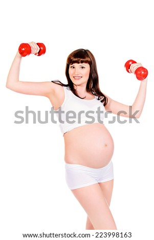 Beautiful pregnant woman doing exercise with dumbbells. Healthcare. Isolated over white.