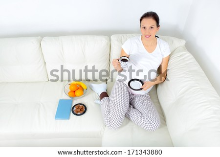 Beautiful pregnant woman drinking coffee on sofa at home - stock photo