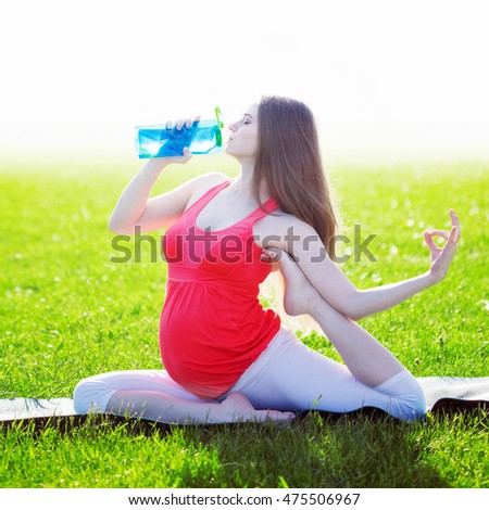 Beautiful pregnant woman drinking water in yoga pose