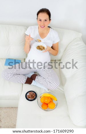 Beautiful pregnant woman eat cereals  on sofa at home - stock photo
