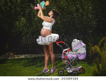 Beautiful pregnant woman having fun in garden  - stock photo