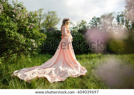 Beautiful pregnant woman holding belly in spring garden. Pregnancy of beauty female person