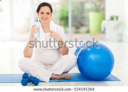 beautiful pregnant woman holding bottle of water - stock photo