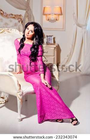 Beautiful pregnant woman in a luxury evening dress sits on a chair. - stock photo