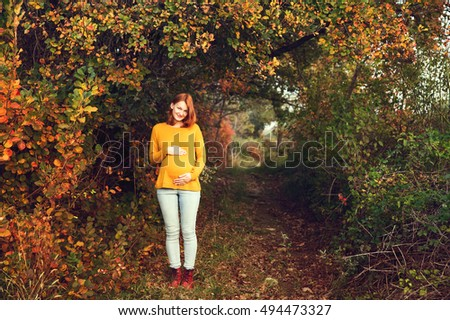 Beautiful pregnant woman in autumn. Photo of healthy pregnancy. 