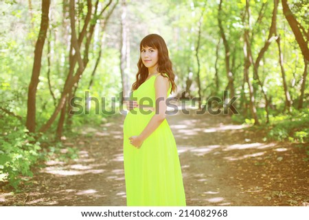 Beautiful pregnant woman in dress in the fabulous forest - stock photo