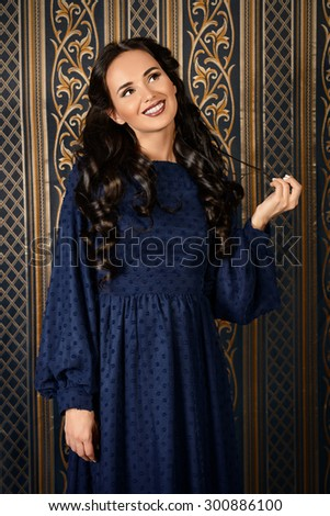 Beautiful pregnant woman in elegant evening dress posing over vintage background. Fashion shot. - stock photo
