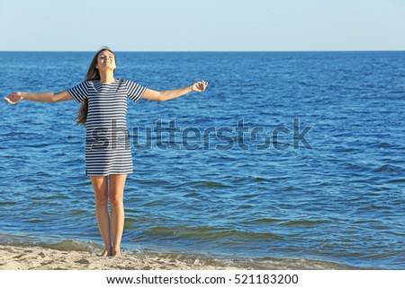 Beautiful pregnant woman in striped dress standing on the beach