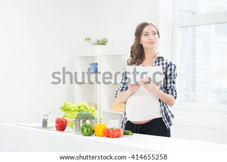 Beautiful pregnant woman in the kitchen surfing in tablet. - stock photo