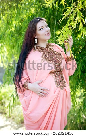 Beautiful pregnant woman in the park. Indian girl in dress outdoor. Pregnant woman feeling the baby.  - stock photo