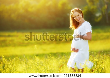 beautiful pregnant woman in the summer nature meadow with yellow flowers - stock photo