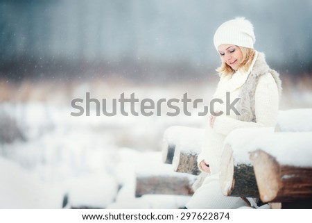 beautiful pregnant woman in white hat and sweater standing outside near the wooden logs and holding her belly at winter time