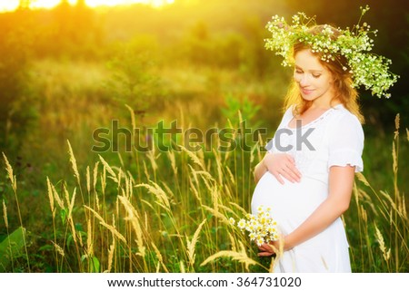 beautiful pregnant woman in wreath  relaxing in the summer nature meadow with sunset - stock photo