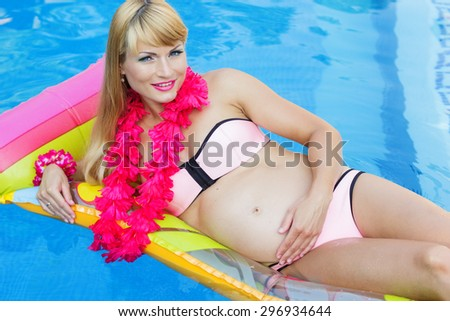 Beautiful pregnant woman is wearing pink hawaiian flowers lying on colorful mattress in blue water of swimming pool, summer vacations