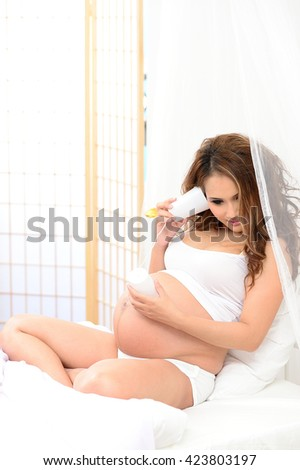 Beautiful pregnant woman listening her belly over white background