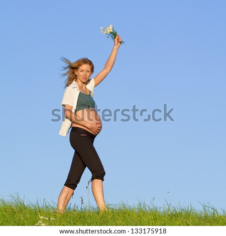 beautiful pregnant woman on a meadow with blue sky