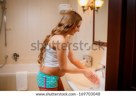 Beautiful pregnant woman on modern bathroom washing her hands