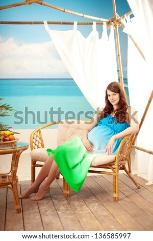 Beautiful pregnant woman on the beach in bungalow