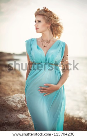 Beautiful pregnant woman outdoor in Greek goddess style with her tummy on sunset  near sea. Young happy girl showing her belly and waiting for little baby. Pregnancy concept. Gorgeous pregnant lady - stock photo