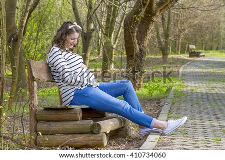 Beautiful pregnant woman outdoor in the park on bench. - stock photo