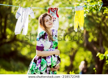 Beautiful pregnant woman outside, human pregnancy - stock photo