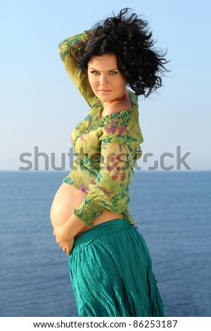 Beautiful pregnant woman over sky background, outdoors - stock photo